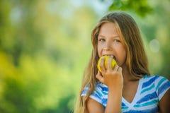 Adolescente que muerde una manzana Fotografía de archivo