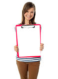 Adolescente que muestra el documento en blanco sobre el sujetapapeles Fotografía de archivo