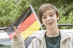 Adolescente que muestra el gesto de la victoria delante de a Foto de archivo