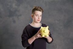 Adolescente que muestra el piggybank Fotografía de archivo