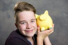 Adolescente que muestra el piggybank Fotos de archivo