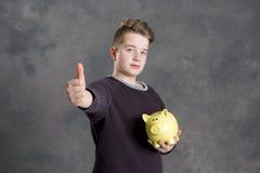 Adolescente que muestra el piggybank y el pulgar para arriba Imagenes de archivo