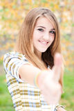 Adolescente que muestra el pulgar para arriba el día del otoño Foto de archivo libre de regalías