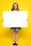 Adolescente que muestra la cartelera en blanco blanca Fotos de archivo