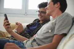 Adolescente que muestra a su amigo la pantalla de su smartphone Imagen de archivo