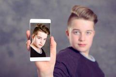 Adolescente que muestra su teléfono Imagen de archivo libre de regalías