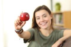 Adolescente que muestra una manzana en casa Imágenes de archivo libres de regalías