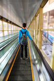 Adolescente que mueve encendido la escalera móvil Foto de archivo libre de regalías