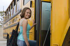 Adolescente que obtem no ônibus escolar Fotos de Stock