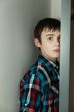 Adolescente que oculta detrás de puerta abierta en hogar Fotografía de archivo libre de regalías