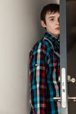 Adolescente que oculta detrás de puerta abierta en hogar Foto de archivo