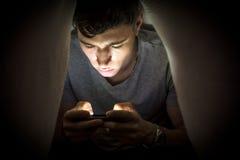 Adolescente que oculta mientras que usa un teléfono móvil Imágenes de archivo libres de regalías