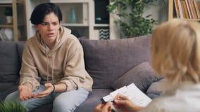 Adolescente que pasa la evaluación psicológica que habla con el terapeuta en oficina almacen de video