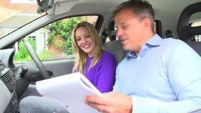Adolescente que pasa la prueba de conducción con el examinador metrajes