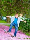 Adolescente que patina en parque floreciente Imágenes de archivo libres de regalías
