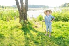 Adolescente que pesca con caña alegre con la caña de pescar verde hecha a mano de la ramita a disposición Fotografía de archivo libre de regalías