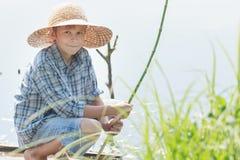 Adolescente que pesca con caña con la caña de pescar verde hecha a mano de la ramita Fotografía de archivo