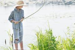 Adolescente que pesca con caña que mira la caña de pescar verde hecha a mano de la ramita en sus brazos Foto de archivo libre de regalías