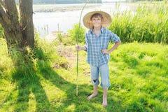 Adolescente que pesca con caña sonriente con la caña de pescar verde hecha a mano de la ramita a disposición Imagenes de archivo