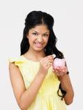 Adolescente que pone el dinero en la hucha Imagen de archivo libre de regalías