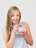 Adolescente que pone el dinero en la hucha Fotografía de archivo libre de regalías