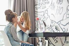 Adolescente que pone el lápiz labial en hermana en casa Imágenes de archivo libres de regalías