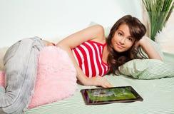 Adolescente que pone en cama con el ordenador de la tablilla Foto de archivo