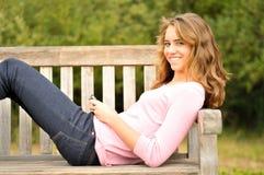 Adolescente que pone en el banco texting Fotos de archivo libres de regalías