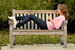 Adolescente que pone en el banco texting Foto de archivo