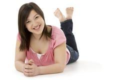Adolescente que pone en el estómago Fotografía de archivo libre de regalías