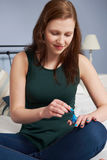 Adolescente que pone en esmalte de uñas Fotografía de archivo