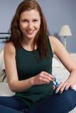 Adolescente que pone en esmalte de uñas Imágenes de archivo libres de regalías