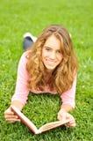 Adolescente que pone en la hierba que lee un libro Imagen de archivo libre de regalías