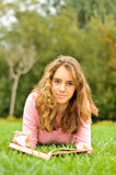 Adolescente que pone en la hierba que lee un libro Imágenes de archivo libres de regalías