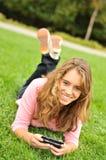 Adolescente que pone en la hierba texting Imagen de archivo