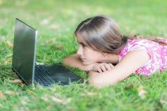 Adolescente que pone en la hierba y que usa su ordenador portátil Fotografía de archivo