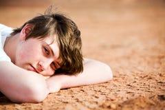 Adolescente que pone en la tierra Imagen de archivo