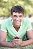Adolescente que pone en mensaje de texto de la lectura del parque en el teléfono móvil Fotografía de archivo libre de regalías