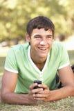 Adolescente que pone en mensaje de texto de la lectura del parque en el teléfono móvil Fotos de archivo libres de regalías