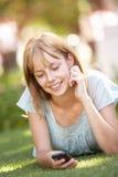 Adolescente que pone en parque usando el teléfono móvil Foto de archivo