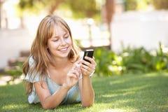Adolescente que pone en parque usando el teléfono móvil Imágenes de archivo libres de regalías