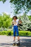 Adolescente que pone en su engranaje patinador Fotos de archivo libres de regalías