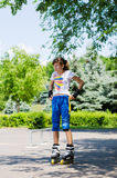 Adolescente que pone en su engranaje patinador Fotos de archivo