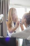 Adolescente que pone maquillaje en hermana en casa Fotografía de archivo