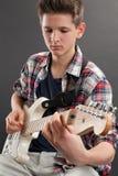 Adolescente que practica la guitarra eléctrica Foto de archivo