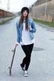 Adolescente que presenta con el monopatín Imagen de archivo libre de regalías