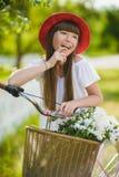 Adolescente que presenta con la bicicleta en el fondo del jardín Foto de archivo libre de regalías