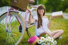 Adolescente que presenta con la bicicleta en el fondo del jardín Fotografía de archivo