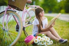 Adolescente que presenta con la bicicleta en el fondo del jardín Imagen de archivo libre de regalías