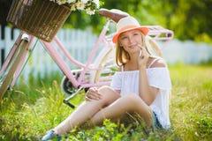 Adolescente que presenta con la bicicleta en el fondo del jardín Fotografía de archivo libre de regalías